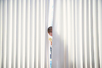 Girl (5-6) peeking from behind blinds