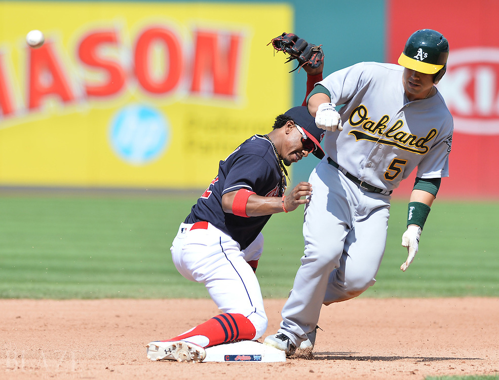 Jul 31, 2016; Cleveland, OH, USA; Oakland Athletics center fielder Jake Smolinski (5) slides into second with a double as Cleveland Indians shortstop Francisco Lindor (12) can't handle the throw during the seventh inning at Progressive Field. Mandatory Credit: Ken Blaze-USA TODAY Sports