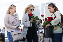 "© Licensed to London News Pictures. 11/06/2017. LONDON, UK.  Red roses are handed to Londoners and tourists on London Bridge. 1,000 red roses with messages of ""love and solidarity"" were given to passers by on London Bridge today.  Photo credit: Vickie Flores/LNP"