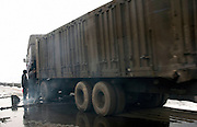 Truck drivers on the side of a road. Days and nights hundreds of truck drivers are conveying coal. This Province is China's largest coal supplier with 500 millions of tonnes each year. It is also the most polluted of the country. Roads and trucks are covered with coal.