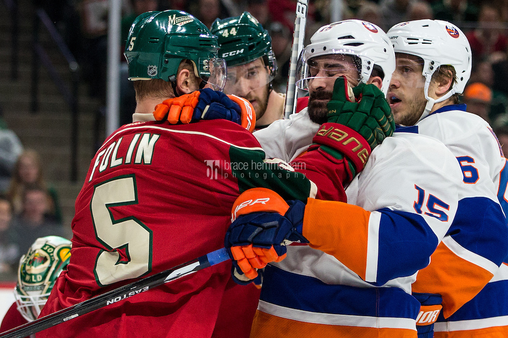 Dec 29, 2016; Saint Paul, MN, USA; Minnesota Wild defenseman Christian Folin (5) grabs New York Islanders forward Cal Clutterbuck (15) after the whistle during the first period at Xcel Energy Center. Mandatory Credit: Brace Hemmelgarn-USA TODAY Sports