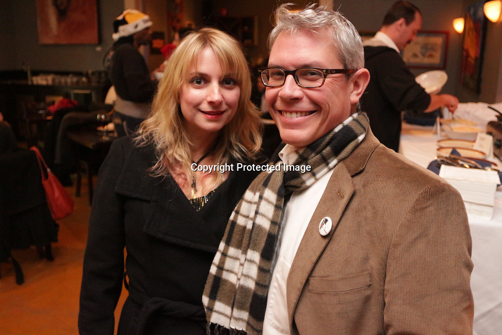 Nina Bays, left, and Bryan Cournoyer pose for a picture Sunday December 21, 2014 during the Brooklyn Arts District Christmas party at Canape in Wilmington, N.C. (Jason A. Frizzelle)