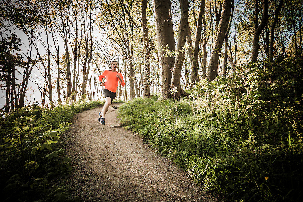 A yong man running on a trail  through the forest in Discovery Park, Seattle, Washington, USA.