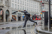 UNITED KINGDOM, London: 28 April 2020 <br /> A member of the public plays up to the camera as he jumps over a puddle on Regent's Street in central London during a wet and miserable afternoon. The weather is set to stay wet for the next few days according to the Met Office.