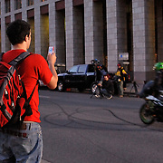 Motorcyles perform high speed stunt rides on 13th Avenue between the Denver Library and the Denver Art Museum.; A young observer is filming a YouTube moment of the action while he is being filmed.  Mediated access........the new way of experiencing life.