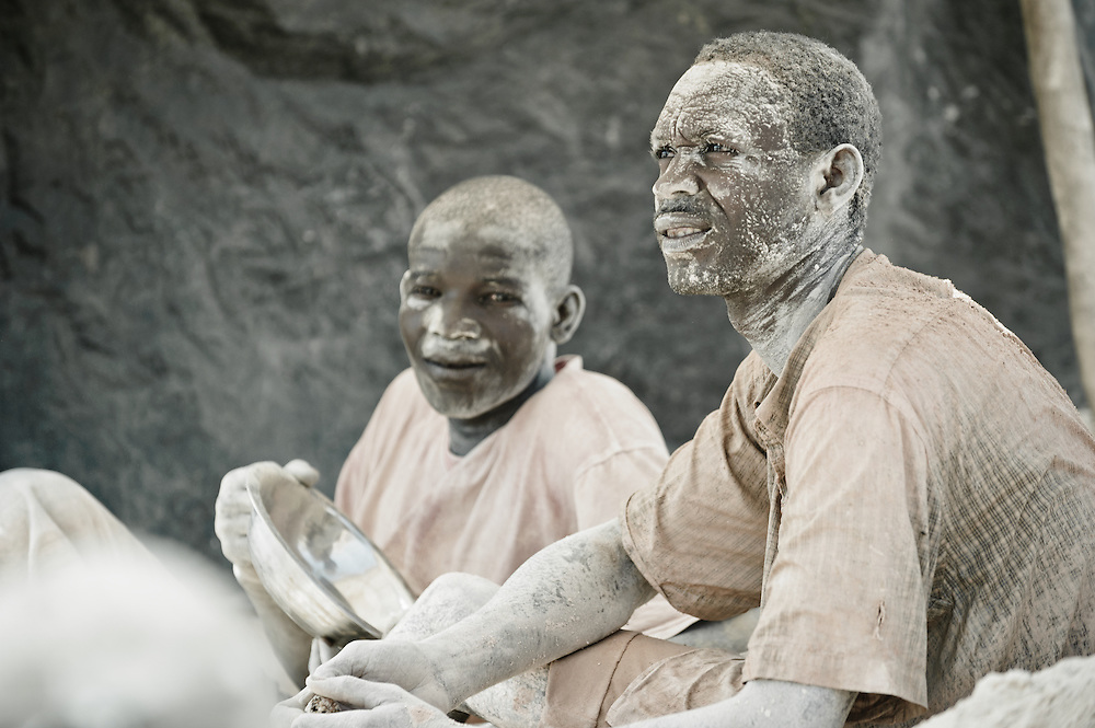 Stock photograph of a African gold miners in Burkina Faso, exhausted and covered in mud from a day down the shaft digging for ore.