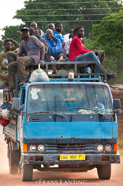 Men hitching ride on overloaded truck, Wechiau, Ghana