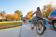 Merrick, New York, USA. Nov. 11, 2016. On Election Day, a family, a mother, father, and two young daughters, rode their bicycles to the polling place at the Park Avenue Elementary school are then were walking their bikes on the front sidewalk as they left the school property.