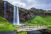 Seljalandsfoss is one of the most famous waterfalls of Iceland. This waterfall of the river Seljalandsá drops 60 metres over the cliffs of the former coastline. It is possible to go behind the waterfall | Seljalandsfoss er en av de mest kjente fossene på Island. Fossen fra elva Seljalandsá har et fritt fall på 60 meter, og treffer det som i sin tid var den gamle kystlinjen. Det er mulig å gå bak fossen.