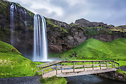 Seljalandsfoss is one of the most famous waterfalls of Iceland. This waterfall of the river Seljalandsá drops 60 metres over the cliffs of the former coastline. It is possible to go behind the waterfall | Seljalandsfoss er en av de mest kjente fossene på Island. Fossen fra elva Seljalandsá har et fritt fall på 60 meter, og treffer det som i sin tid var den gamle kystlinjen. Det er mulig å gå bak fossen.