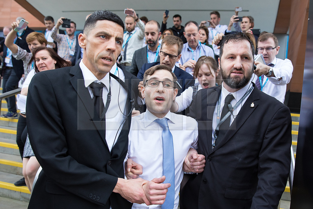 © Licensed to London News Pictures . 04/10/2017. Manchester, UK. Stunt comedian SIMON BRODKIN (aka Lee Nelson ) is ejected from the Conservative Party Conference security guards , pursued by dozens of reporters waving mobile phones . Brodkin handed Prime Minister Theresa May a P45 form during a calamitous keynote speech on the fourth and final day of the Conservative Party Conference . Brodkin said Boris Johnson told him to do it . Photo credit : Joel Goodman/LNP