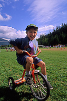 Boy, 6-8, rides a tricycle in an outdoor sports day event at school.