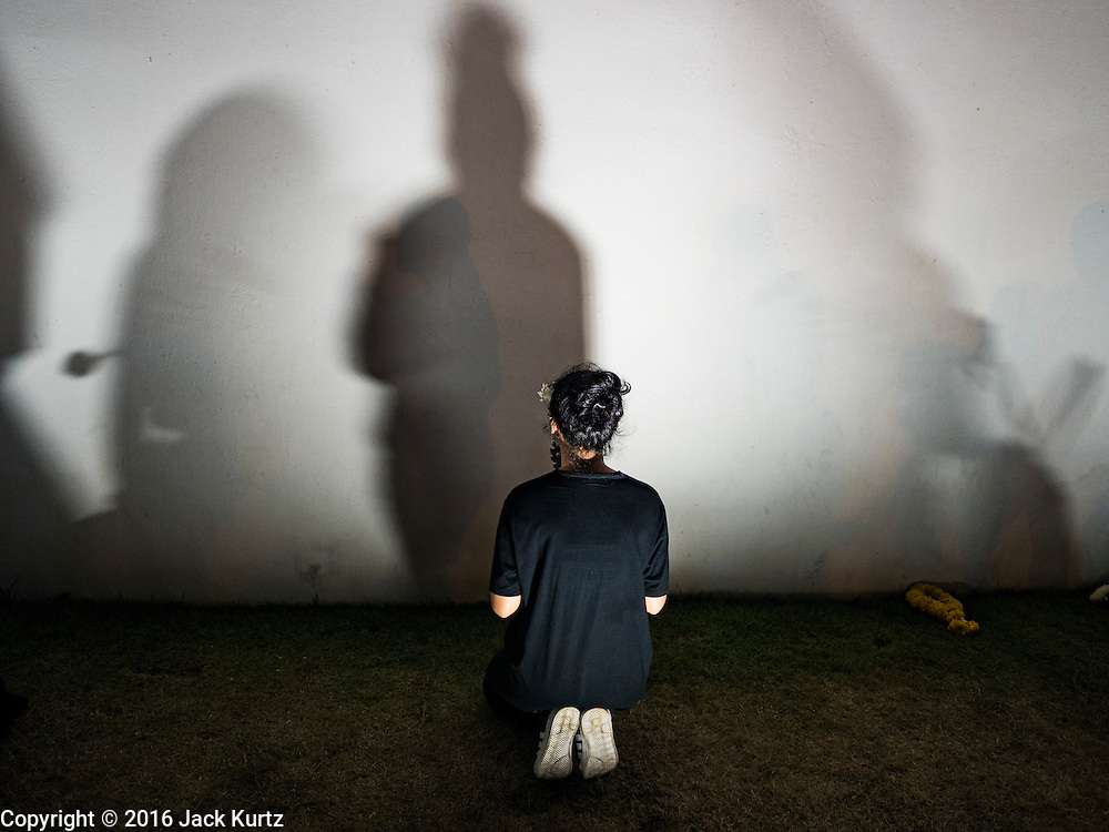 20 OCTOBER 2016 - BANGKOK, THAILAND: A man in mourning for the death of Bhumibol Adulyadej, the King of Thailand, prays at the wall of the Grand Palace in Bangkok. Sanam Luang, the Royal Ceremonial Ground, is packed with people mourning the Monarch's death. The King died Oct. 13, 2016. He was 88. His death came after a period of failing health. Bhumibol Adulyadej was born in Cambridge, MA, on 5 December 1927. He was the ninth monarch of Thailand from the Chakri Dynasty and is also known as Rama IX. He became King on June 9, 1946 and served as King of Thailand for 70 years, 126 days. He was, at the time of his death, the world's longest-serving head of state and the longest-reigning monarch in Thai history.        PHOTO BY JACK KURTZ