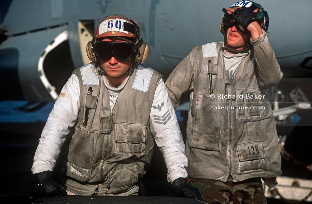 Dirty US Nacy crewmen on the deck of US Navy aircraft carrier USS Harry S Truman during its deployment patrol of the no-fly zone at an unknown location in the Persian Gulf, on 8th May 2000, in the Persian Gulf. The Truman is the largest and newest of the US Navy's fleet of new generation carriers, a 97,000 ton floating city with a crew of 5,137, 650 are women. (Photo by Richard Baker / In Pictures via Getty Images)