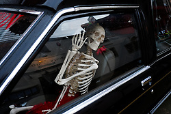 © Licensed to London News Pictures. <br /> 01/11/2014. <br /> <br /> Whitby, Yorkshire, United Kingdom<br /> <br /> A skeleton waves from a hearse parked on a street during the Whitby Goth Weekend. <br /> <br /> The event this weekend brings together thousands of extravagantly dressed followers of Victoriana, Steampunk, Cybergoth and Romanticism who all visit the town to take part in celebrating Gothic culture. This weekend marks the 20th anniversary since the event was started by local woman Jo Hampshire.<br /> <br /> Photo credit : Ian Forsyth/LNP