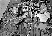 Julie Goodyear, better known as Bet Lynch, landlady of Coronation Street's Rover's Return, joins British soldiers serving in N Ireland for a pint after the opening of a traditional English pub at Ballykinlar Army Camp, N Ireland.  197212160826a, 825/72.<br /> <br /> Copyright Image from Victor Patterson, 54 Dorchester Park, Belfast, UK, BT9 6RJ<br /> <br /> t1: +44 28 9066 1296 (from Rep of Ireland 048 9066 1296)<br /> t2: +44 28 9002 2446 (from Rep of Ireland 048 9002 2446)<br /> m: +44 7802 353836<br /> <br /> victorpattersonbelfast@gmail.com<br /> victorpatterson@me.com<br /> <br /> www.victorpatterson.com<br /> <br /> Please see my Terms and Conditions of Use at https://www.victorpatterson.com/page2<br /> It is IMPORTANT that you familiarise yourself with them.<br /> <br /> Images used on the Internet incur an additional cost and must be visibly watermarked i.e. © Victor Patterson within the body of the image and copyright metadata must not be deleted. Images used on the Internet have a size restriction of 4kbs and are chargeable at rates available at victorpatterson.com.<br /> <br /> This image is available only for the use of the download recipient i.e. television station, newspaper, magazine, book publisher, etc, and must not be passed on to any third party. It is also downloaded on condition that each and every usage is notified within 7 days to victorpatterson@me.com<br /> <br /> The right of Victor Patterson (or the named photographer) to be identified as the author is asserted in accordance with The Copyright Designs And Patents Act (1988). All moral rights are asserted.