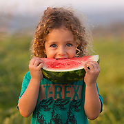 Summer taste young child enjoys a sweet, red, cold watermelon Model Release Available
