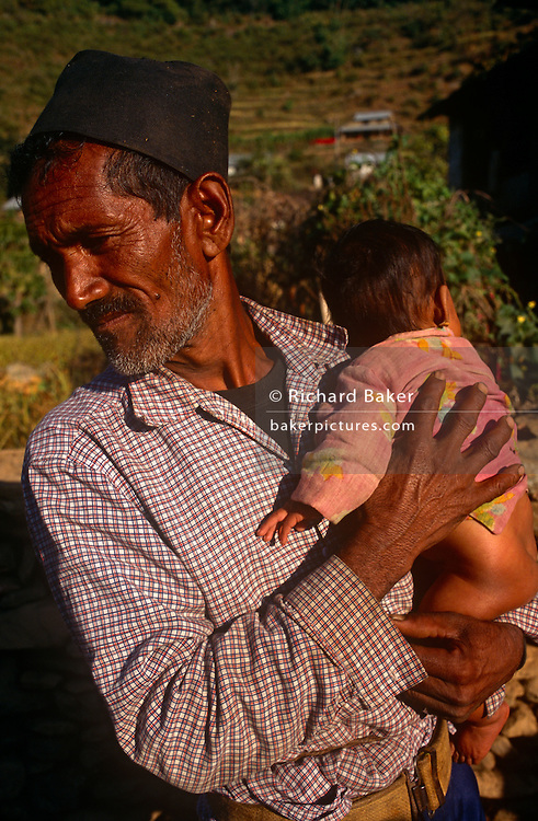 An old man holds a young child near their home in the central region of the Himalayan mountain kingdom of Nepal. We see the dark skin of this working man in a foothill dwelling near the town of Gorkha where the British army traditionally find young men for the Gurkha regiment (as thay have done since 1857). The prospects for the child may mean it will in future try to seek work in the cities like Kathmandu rather than face a lifetime's struggle in local agriculture. Their supplies and contact with the outside world comes up from tracks of boulders and stone along which either men or yaks carry up food for basic survival and luxury goods.