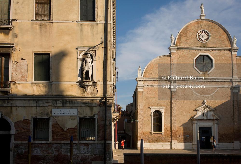 A woman looks out from the shadows of a narrow street at the Santa Maria dei Carmini church on the Rio de San Margherita canal in Dorsoduro, a district of Venice, Italy.