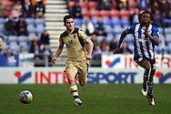 Lewis Cook of Leeds United (l) and Gaetan Bong of Wigan Athletic chase the ball. Skybet football league championship match , Wigan Athletic v Leeds Utd at the DW Stadium in Wigan, Lancs on Saturday 7th March 2014.<br /> pic by Chris Stading, Andrew Orchard sports photography.