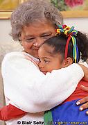 Grandmother hugs grandchild at home