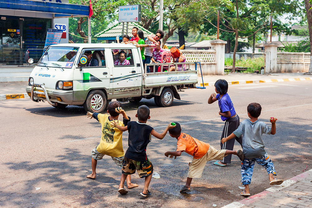 A group of young boys throw water bombs at a passing truck during Lao New Year celebrations in Vientiane, Laos.
