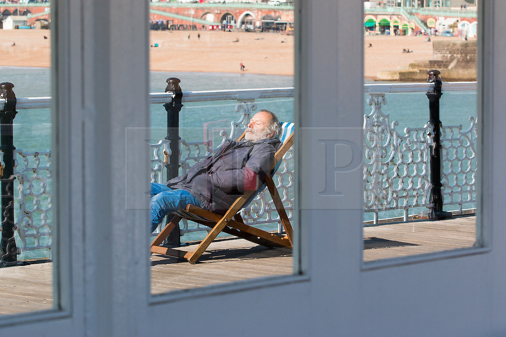 © Licensed to London News Pictures. 14/03/2016. Brighton, UK. A member of the public relaxes in the sunshine on Brighton pier. Photo credit: Hugo Michiels/LNP