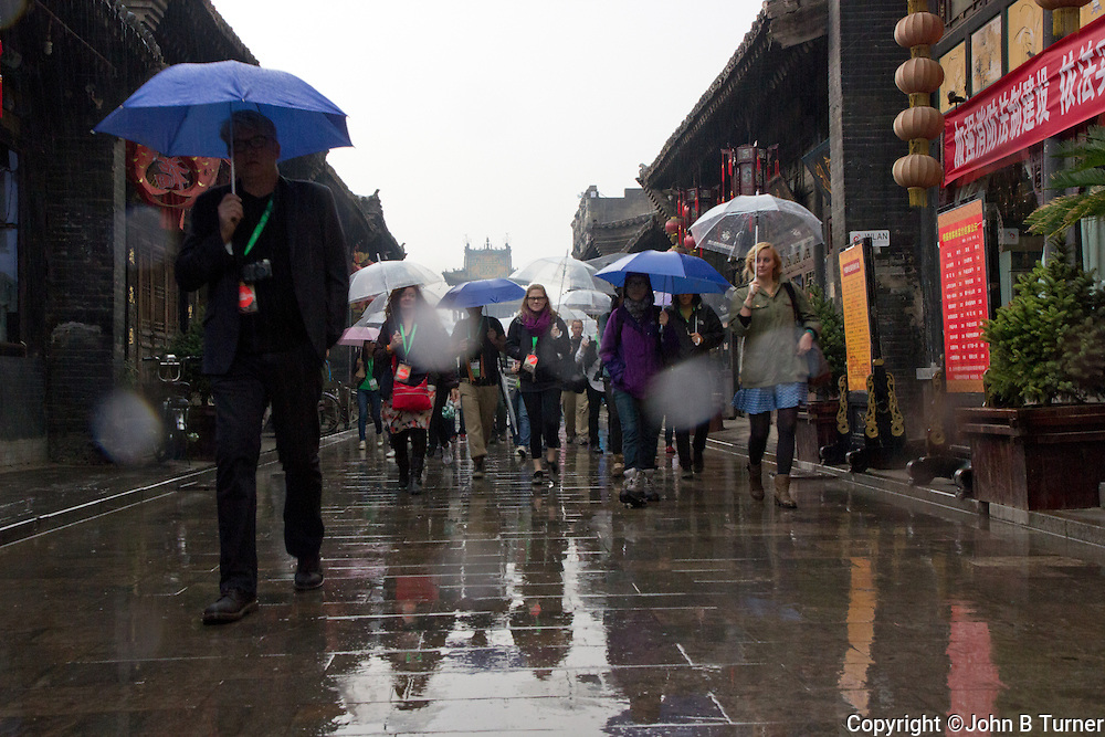 Rain affected the start, but not the spirit of the spectacular opening ceremony of the Pingyao International Festival of Photography September 2012. This series follows a contingent of guest foreign photographers and curators from their hotel to the ceremony and back again. The huge annual festival, showcasing hundreds of photographers and thousands of images, is sponsored by the Shanxi Province and central government as a showcase for both photography and the ancient city of Pingyao which makes good use of old factory interiors and exteriors as display spaces.