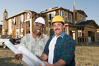 Two men holding blueprints at construction site, portrait