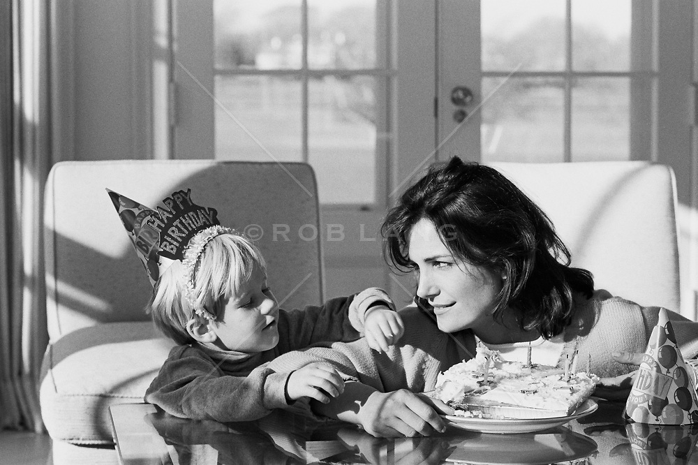 little boy reaching for his birthday cake next to his mom