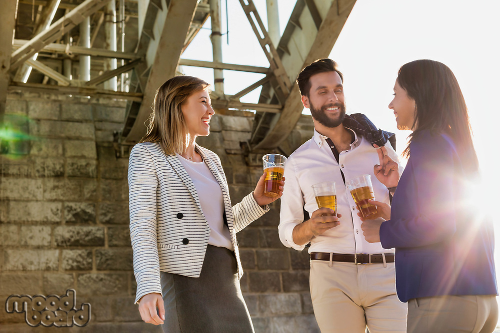 Business people celebrating success while drinking beer with lens flare in background