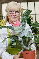 Portrait of a happy senior woman holding pot plant