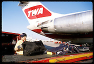 Worker loads baggage from arriving TWA jet into luggage cart at Lambert Intl Airport; St. Louis. Missouri
