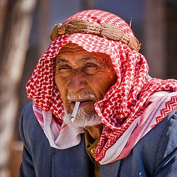 Old man with headscarf smoking in the street, Sanliurfa, Turkey, Asia