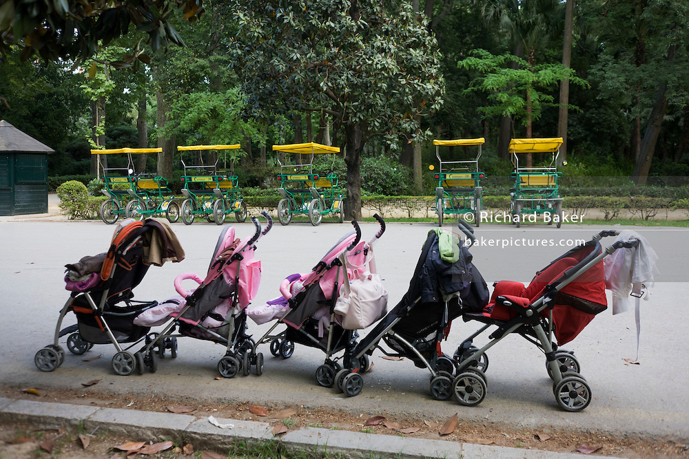 Five childrens' buggies line up in front of 5 park rental carriages in Seville's Parque de Marie Luisa.