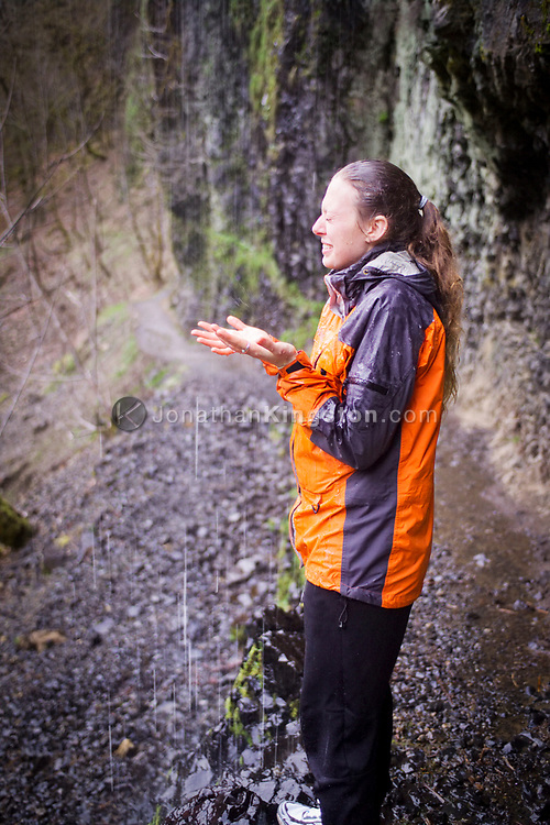 COLUMBIA RIVER GORGE, OR:  In a playful mood a woman stands under a small waterfall while hiking the Eagle Creek trail in the Columbia River Gorge, Portland, Oregon. Trail runners, day hikers, kayakers and other outdoor enthusiasts enjoy the many recreational opportunities that the Columbia River Gorge affords to local residents and tourists alike. (Model Released)