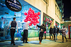 © Licensed to London News Pictures . 14/02/2016 . Manchester , UK . Staff from an Italian restaurant release red balloons , which had been used as Valentine's Day decorations , in the street outside . Revellers in Manchester out overnight on Valentine's Day evening . Photo credit : Joel Goodman/LNP