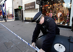 © Licensed to London News Pictures. 20/12/2011. London, United Kingdom .A police officer cordens off the area after an attempted robbery on a jewellery shop on Oxford Street by persons on two motorbikes..Photo credit : Chris Winter/LNP