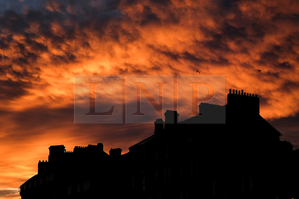 © Licensed to London News Pictures.17/11/15<br /> Saltburn, UK. <br /> <br /> A spectacular sunrise lights up clouds over houses on the east coast of England at Saltburn in Cleveland.<br /> <br /> Photo credit : Ian Forsyth/LNP