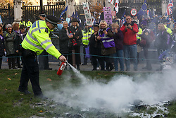 © Licensed to London News Pictures. 05/11/2019. London, UK. Police uses a fire extinguisher to put out the flames of a burning effigy as Women's Pension reformers demonstrate outside Parliament by burning an effigy of Pension's Minister Guy Opperman on Parliament Square. The Pensions act increases the female state pension age from 60-65. Photo credit: Alex Lentati/LNP