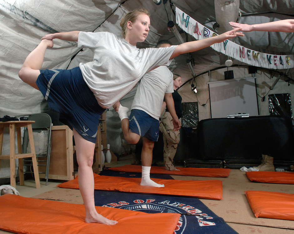 Balad Air Base, Iraq -- Staff Sgt. Bonnie Mc Kinley leads yoga classes during a break in her 15-hour shift at the Air Force Theater Hospital, Balad Air Base, Iraq.  The 5'4&quot; respiratory therapist with the 332 Expeditionary Medical Group weights in at 140 pounds, but a few years ago she weighed 215 pounds after a pregnancy. She attributes her weight loss and fitness increase to the practice of yoga and a healthy diet. The bending and stretching worked so well for her that she achieved certification as a instructor and leads yoga sessions for base personnel, three times a week, in the hospital staff lounge. Stationed at Sheppard Air force Base, Texas, she is finishing up a deployment at the Air Force Theater Hospital at Balad Air Base, Iraq. (U.S. Air Force photo by Master Sgt. Lance Cheung)<br />