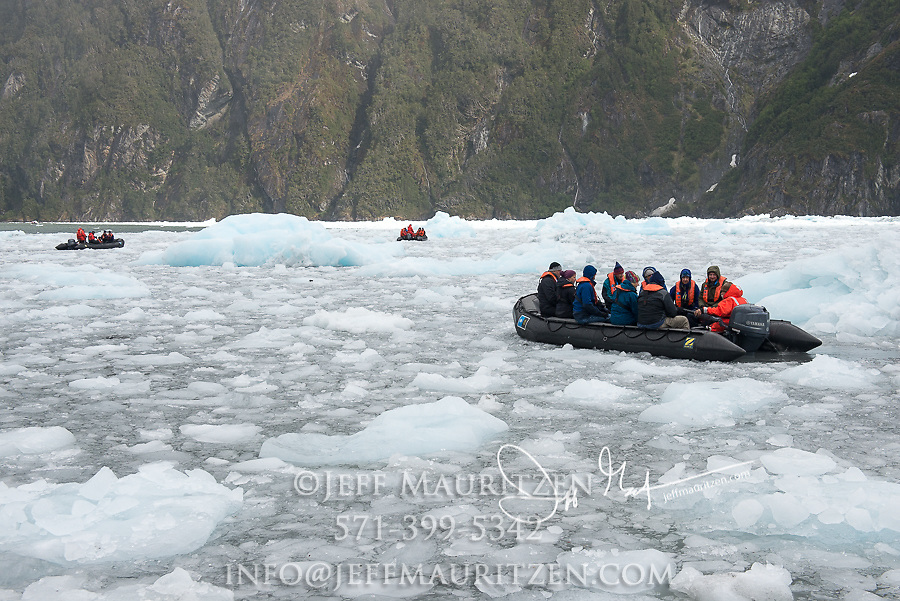Expedition travelers aboard zodiac inflatable boats cruise through glacial ice in Garibaldi fjord in Parque Nacional Alberto de Agostini, Chile.