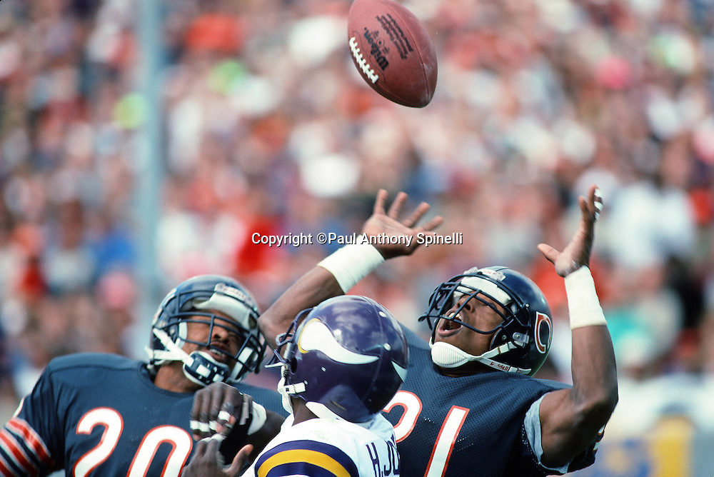 Minnesota Vikings wide receiver Hassan Jones (84) looks behind while Chicago Bears defensive back Mark Carrier (20) and Chicago Bears defensive back Donnell Woolford (21) try to intercept a pass during the NFL football game against the Chicago Bears on Sept, 23, 1990 in Chicago. The Bears won the game 19-16. (©Paul Anthony Spinelli)