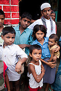 """Sitara's (aged 35, unseen) children Ajman (5, centre bottom), Roshni (10, girl in blue), and Tamanna (8 months, baby) stand with their neighbours outside their house in a village in Allahabad, Uttar Pradesh, India. """"I wish that I could stop getting pregnant but our religion says that children are a gift of God."""" says Sitara, an illiterate muslim lady whose husband works as a vegetable vendor in the local village market. They have resisted all advises of permanent sterilization from the local village-level health workers. In India, male children are preferred and wives are often pressured heavily into trying for more male children immediately after finding out that their newborns are female. Sex determination ultrasounds are illegal in India due to high female foeticide cases. Allahabad, a poorer district of the state of Uttar Pradesh, is the most populated district of the most populous state of India. While Ghaziabad, located close to India's capital city, Delhi, has a population of 4,661,452 with a sex ratio of 878 girls against every 1000 boys, and a high literary percentage of 85%, Allahabad, has a population of 5,959,798 and a sex ratio of 902 girls against every 1000 boys and a literacy rate of 74.41%. Photo by Suzanne Lee / Panos London"""
