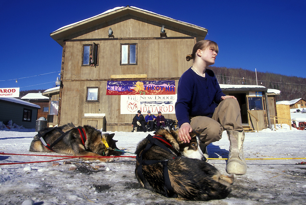 USA, Alaska, Young woman pets sled dogs at Takotna checkpoint during 1998 Iditarod sled dog race