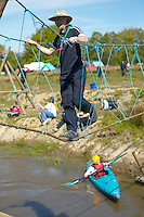 Scouts and scout leader crossing a rope bridge over a river