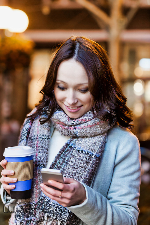 Portrait of young attractive woman holding cup of coffee while using smartphone
