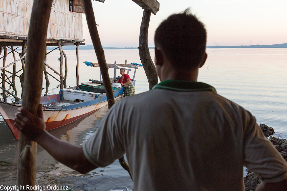 Soon after sunrise, Iwan Setian, 24 (foreground), has just returned from fishing and looks on while his mother Umikalsum, 41, brings his catch from the boat to the family home. They live in Kubur Cina, a neighbordhood of Lewoleba, Nubatukan subdistrict, Lembata district, East Nusa Tenggara province, Indonesia.