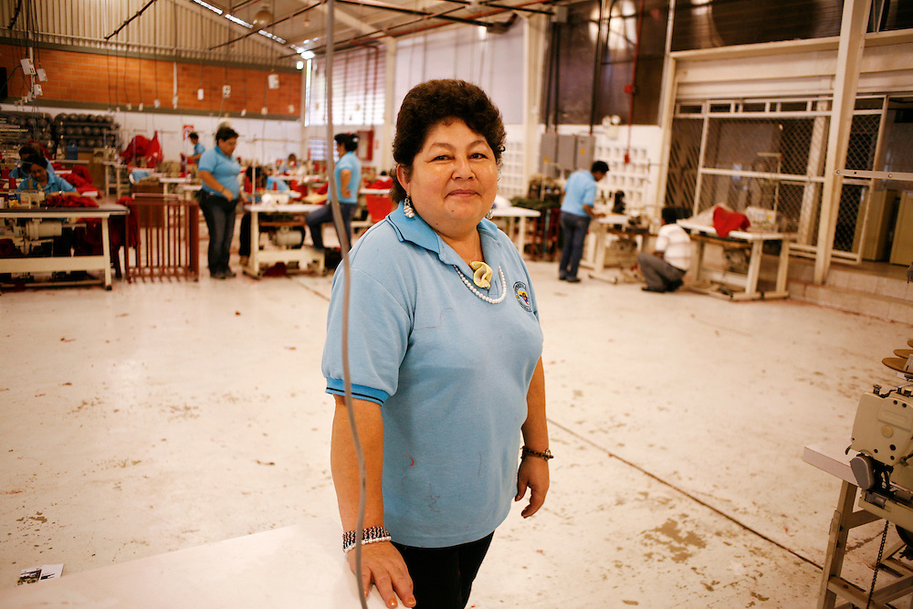 "A worker makes red t-shirts for the government in a factory located in a compound referred to as an ""endogenous zone"" located in Catia barrio (one of the largest barrios in Caracas). The compound is part of the government's plan to build zones for work, entertainment, health care, recreation and other activities and services for nearby residents."