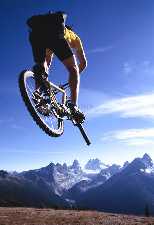 A mountain biker jumps into a view of the Bugaboo Mountains in Canada's British Columbia.